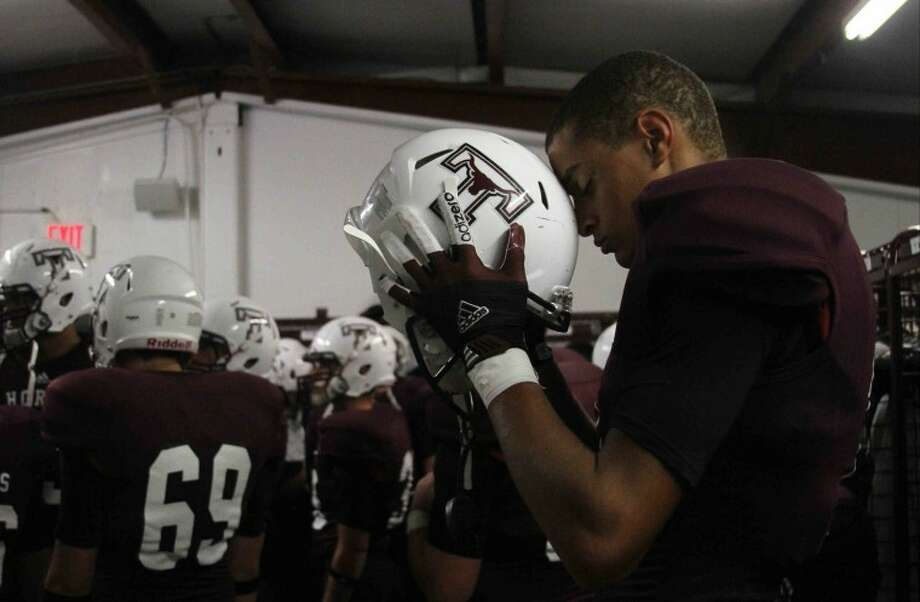 Thoughts: Some images you can't make without access. This is an example of that. Tarkington's head coachBrandon Carpenter was kind enough to allow me to be in the locker room before the game for his pregame speech following warmups. I captured this image right before he came out. The composition and separation of Alex Latham from the rest of the team gives a real intimate feel to the image.Caption: Tarkington wide receiver Alex Latham (11) prays before a high school football game in Tarkington on Sept. 7, 2012. Tarkington defeated Hardin 20-19.