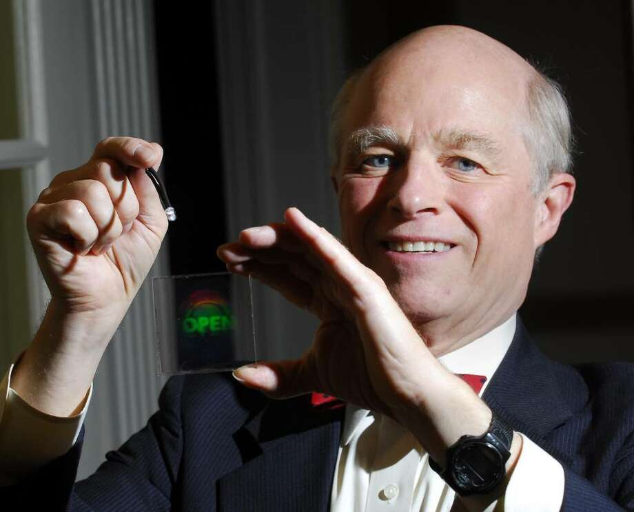 9-1-2009, Stamford Home of R. Douglas McPheters, R. Douglas McPheters, President of HoloTouch Inc., poses with HoloTouch interactive technology which is a touchless holographic image control that floats in the air.  The control pictured here is one which can be used to open a door without having to touch the door or any control panel.  Bob Luckey/Staff Photo Photo: ST