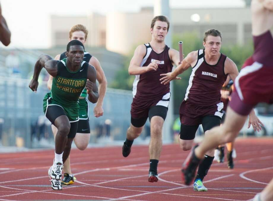 Travis Hanes hands to Stratford teammate Terrence Peters (left) during the 800-meter relay Thursday at Stratford High School. The Spartans finished third in the event, one spot behind John Grunkenmeyer, Jordan Turnbow and Magnolia.