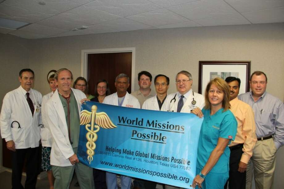 Dr. Thomas Flowers (front, holding sign) and Roxane Richter (right, holding sign), president of WMP, pictured with members of Clear Lake Regional Medical Center's Medical Executive Committee after receiving the donation for the group's upcoming humanitarian mission trip.