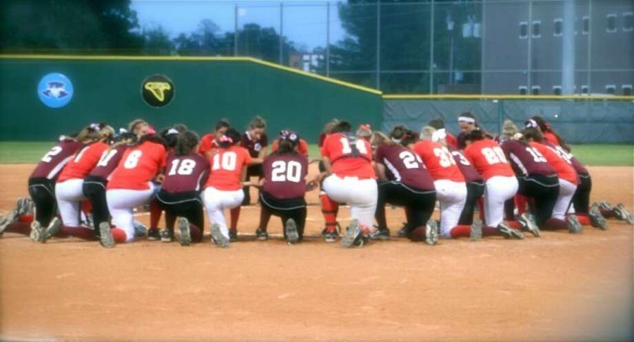 Players of the Cinco Ranch and MacArthur softball teams gather in a prayer circle after umpire Ricky Scearce Jr. collapsed on the field Friday night. He was pronounced dead an hour later.