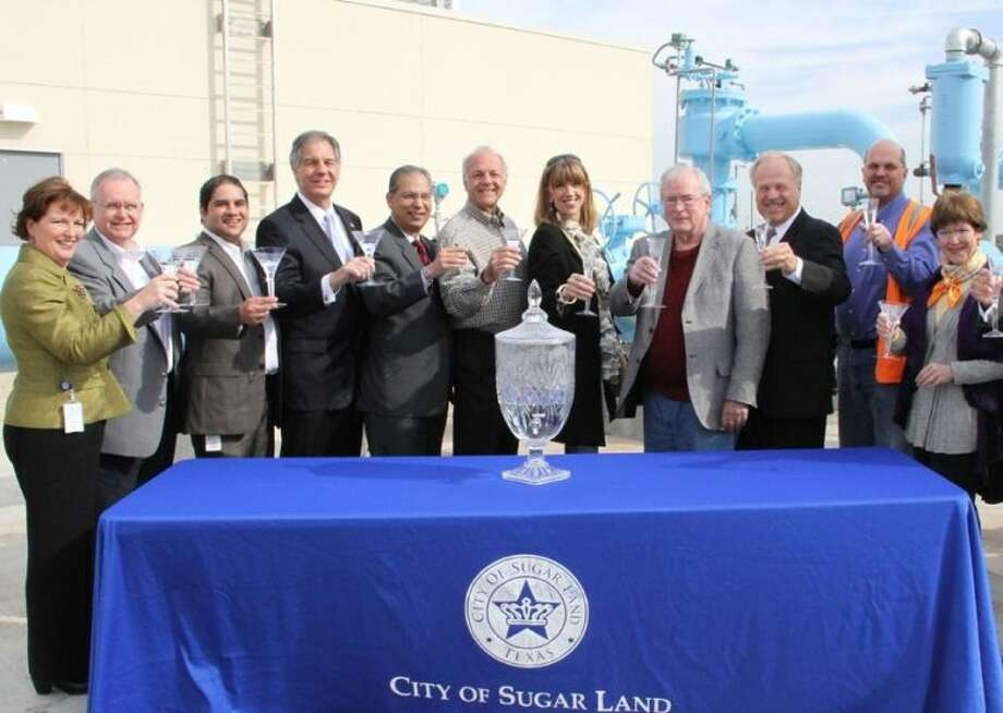 Residents who participated in a taste test on Nov. 8, 2008, returned to sample the final product after Sugar Land placed its new surface water treatment plant in service. The taste test was held at a surface water pilot plant near the banks of Oyster Creek, and it helped the City identify technology to ensure high quality drinking water for residents that looks and tastes great. Sugar Land is using a multi-barrier integrated membrane treatment process at the plant. Pictured (L-R) are Assistant City Manager Karen Daly; Councilmembers Steve R. Porter and Himesh Gandhi; resident Jim Kij; City Councilmember Harish Jajoo; residents John Novak, Yaffa Steubinger and Tom Coughlin; City Manager Allen Bogard; Senior Project Manager Michael Fox; and resident Jane Goodsill. Photo: Courtesy City Of Sugar Land