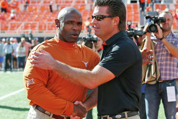 Texas head coach Charlie Strong, left, shakes hands with Oklahoma State head coach Mike Gundy, right, before an NCAA college football game in Stillwater, Okla., Saturday, Oct. 1, 2016. (AP Photo/Sue Ogrocki)