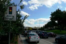 """Though somewhat obscured by foliage, a """"photo enforced"""" sign warns drivers to properly observe traffic lights at the U.S. 59/Highway 6 intersection."""
