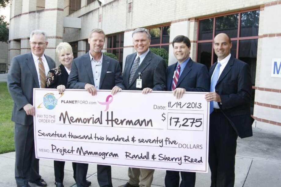 Planet Ford Humble partnered with Memorial Hermann Northeast Hospital and the Northeast Hospital Foundation to donate a portion of their sales of every vehicle to the nonprofit organization, Project Mammogram. Randall Reed, owner of Planet Ford, center, presented to the check to Norman Funderburk, right center, for the local nonprofit organization, Project Mammogram Nov. 19, 2013.
