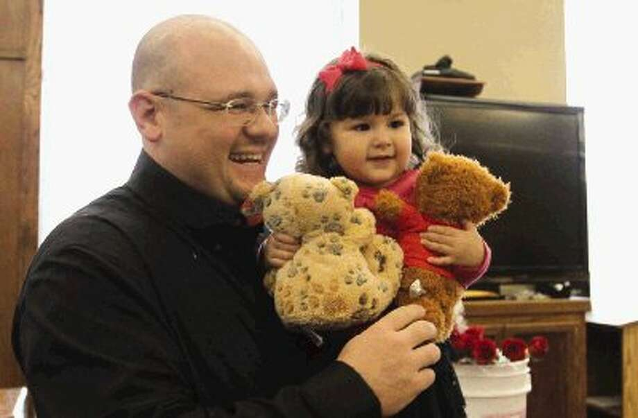 """Lianey Woodard, right, holds a bear as her dad, Scott Woodard, smiles during the annual """"Home for the Holidays"""" event in celebration of National Adoption Day at the Montgomery County Courthouse Wednesday. Judges were on hand to rule in favor of adoptions for families. To view or purchase this photos and others like it, visit HCNPics.com. / Conroe Courier"""