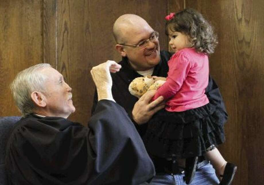 "Lianey Woodard, right, holds a bear as her dad, Scott Woodard, smiles at Judge Jerry Winfree during the annual ""Home for the Holidays"" event in celebration of National Adoption Day at the Montgomery County Courthouse Wednesday. Several judges were on hand to rule in favor of adoptions for families. To view or purchase this photos and others like it, visit HCNPics.com. / Conroe Courier"