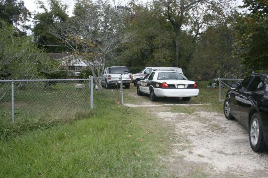 Law enforcement vehicles line the driveway leading up to a property on CR 2212 where 50-75 dogs and cats were voluntarily surrendered on Thursday to the Society for the Prevention of Cruelty to Animals. Photo: STEPHANIE BUCKNER