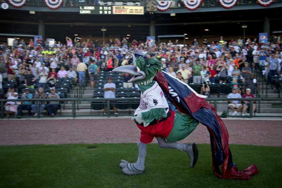 Lou E. Loon runs past fans waving the Midwest League Championship flag after the Great Lakes Loons won the  championship series at Dow Diamond September 18. This is the first time in the team's 10-year history that they won the league title. Photo: Brittney Lohmiller/Midland Daily News