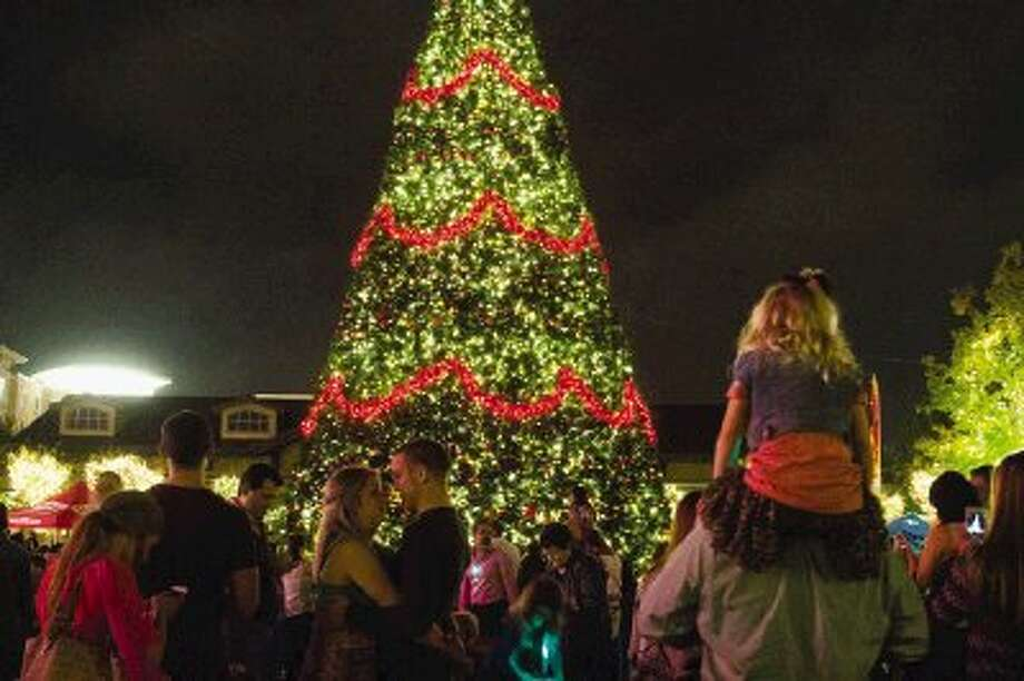 Families gaze at a 70-foot Christmas tree during a tree lighting ceremony at Market Street in The Woodlands on Thursday night. Photo: Staff Photo By Ana Ramirez / The Conroe Courier/ The Woodlands Villager