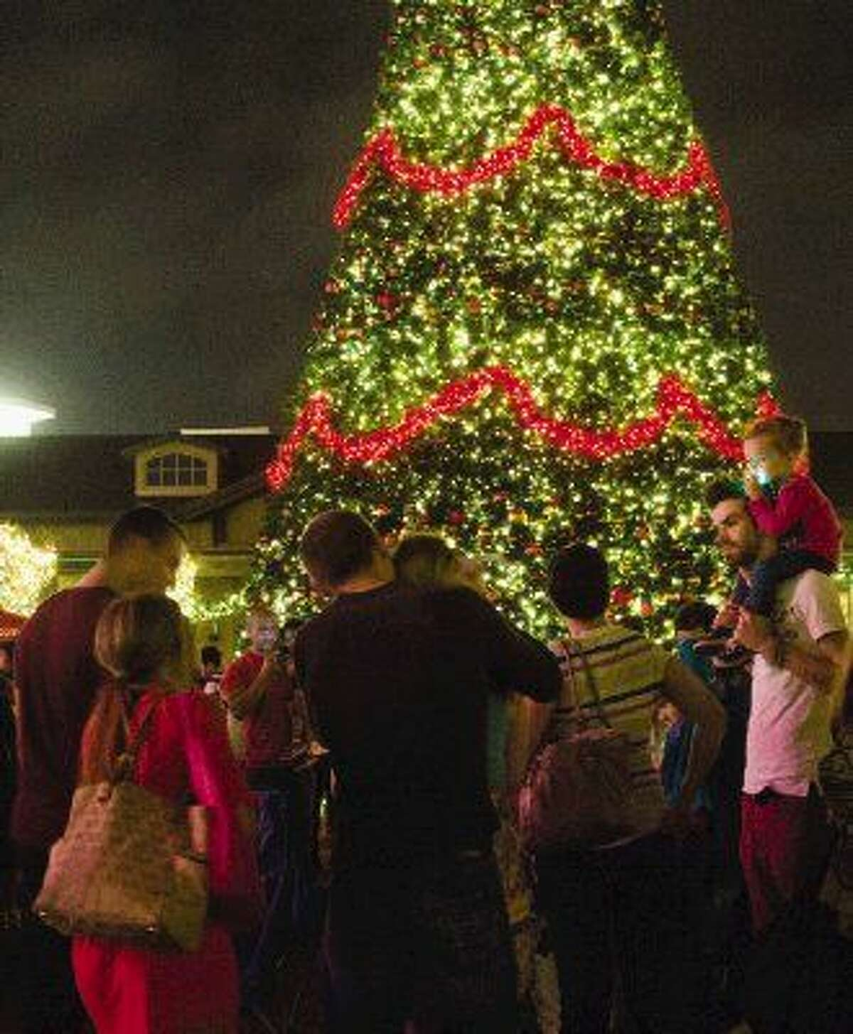 In this 2013 file photo, families gaze at a 70-foot Christmas tree during a tree lighting ceremony at Market Street in The Woodlands.