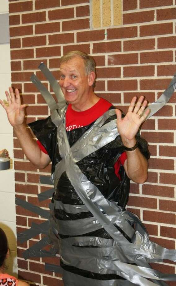 Ed Husk, Northside Elementary Principal, spent two hours duct taped to the wall in a fundraising effort at the school on Friday, Nov. 22. Photo: STACEY GATLIN