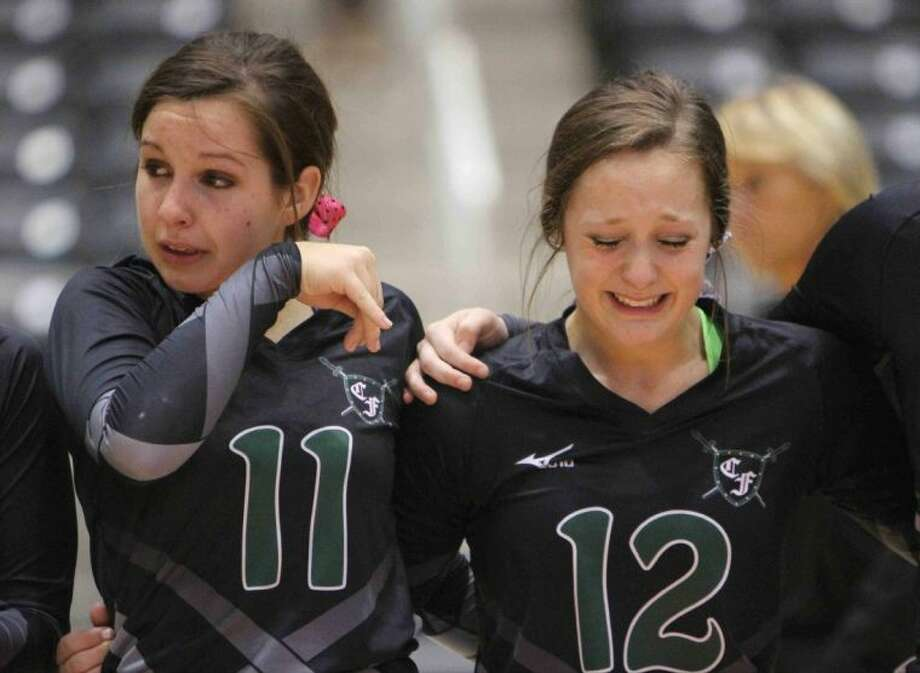 Clear Falls' Madelyn St. Germain (11) and Rachel Bobo (12) can't hold back the tears after losing to The Woodlands in a Class 5A state volleyball semifinal Friday in Garland,. Photo: JASON FOCHTMAN