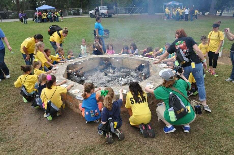 Members of Girl Scout Troop 13514 lead the way in teaching Scouts from the region the basics of camping, like making s'mores.