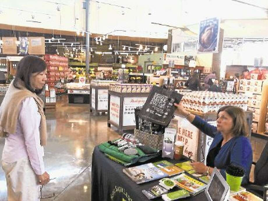 "Keep Sugar Land Beautiful Executive Director Vicki Gist (right) offers a reusable grocery bag to Sugar Land Whole Foods Market shopper Prudence Fong (Left) on Friday, Nov. 15, ""America Recycles Day."" Photo: Zach Haverkamp / @WireImgId=2651437"