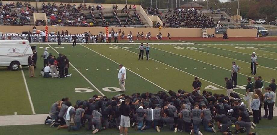 Clear Falls football players all kneel in prayer for an injured Fort Bend Hightower opponent. Photo: JEFF NEWPHER