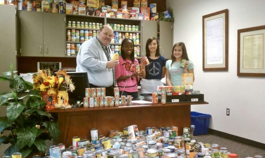 Krimmel Intermediate School Principal Scott Crowe is joined by some students to show off the cabinet-busting amount of cans the school's students collected.