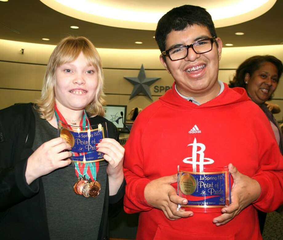 Accepting Point of Pride awards from the Spring ISD Board of Trustees are Spring High School students Rebecca Carkhuff, from left, and Christian Cisneros for being named 2013 Special Olympics Texas Athletes of the Year.