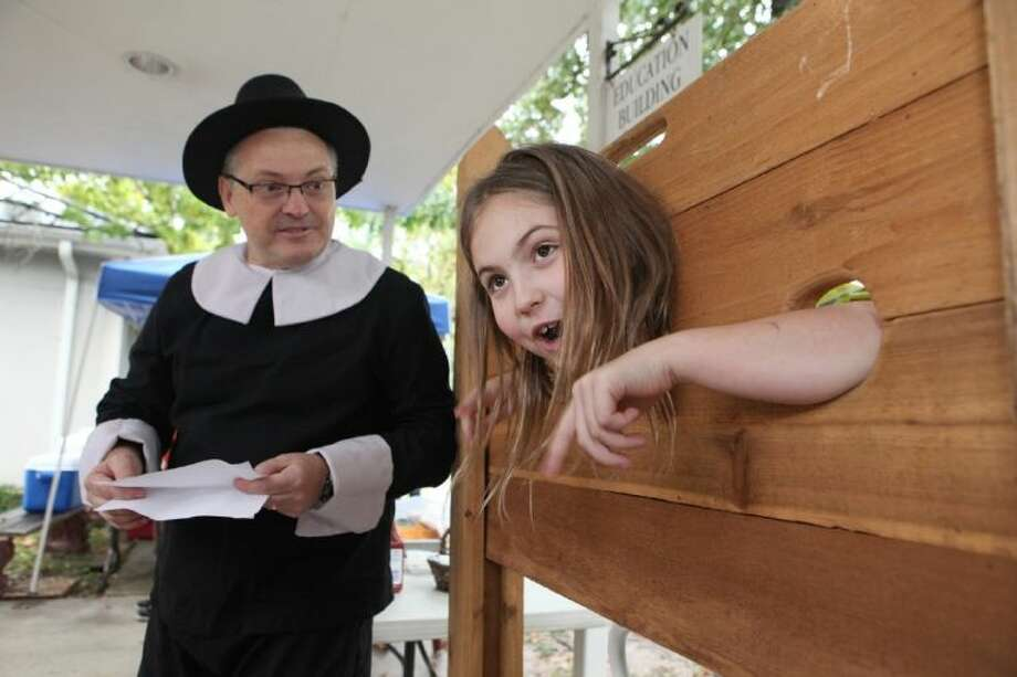Lyla Kortis, 9, has to answer some fun questions from Eric Toskey before getting out of the stockade during the Pilgrim Festival at First Congregational Church. Photo: Alan Warren