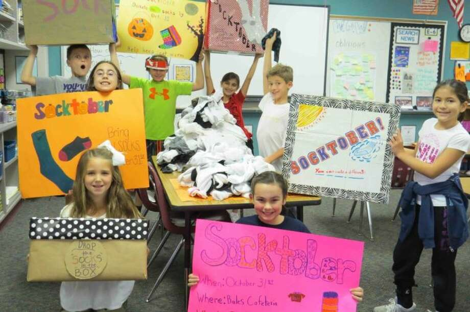 "This year Council delivered cards to two local retirement/nursing homes on Make a Difference Day and delivered socks to the homeless in downtown Houston. Socks were collected through a sock drive as part of ""Socktober."" Students made posters and boxes to get the word out and then sorted all the socks. Photo: Submitted Photo"
