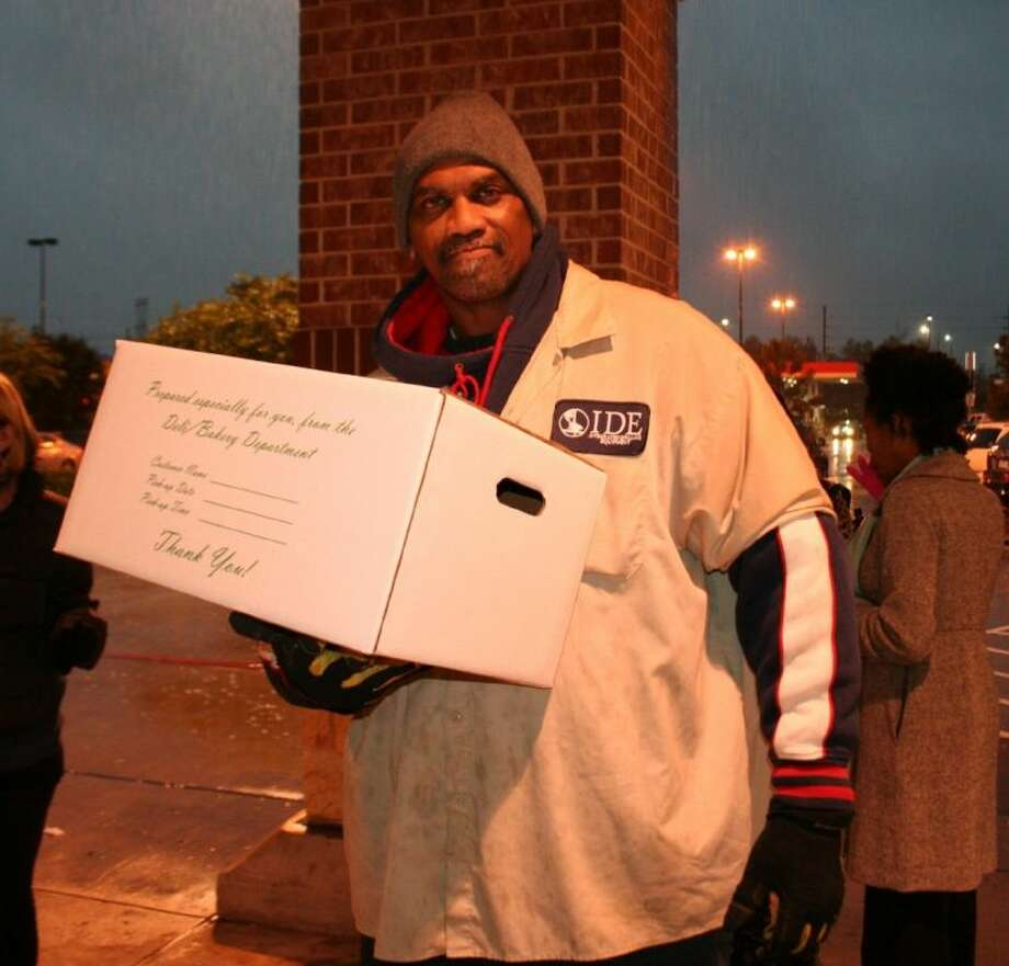 James Kemp receives a Thanksgiving meal provided by Sammy Davis and Kroger Nov. 25, 2013. Photo: Nate Brown