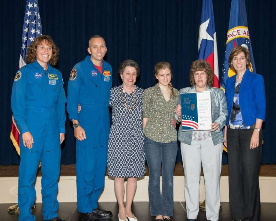 Astronauts Randy Bresnik and Dottie Metcalf-Lindenburger presented Barrios Technology employee Stefany Bartz with the Silver Snoopy Award for his support of NASA's space program. Pictured from left are Dottie Metcalf-Lindenburger, NASA Astronaut; Randy Bresnik, NASA Astronaut; Carol Bartz; Leanne Stepchinski; Stefany Bartz; and Ellen Ochoa, JSC Center Director. Photo: NASA-Bill Stafford