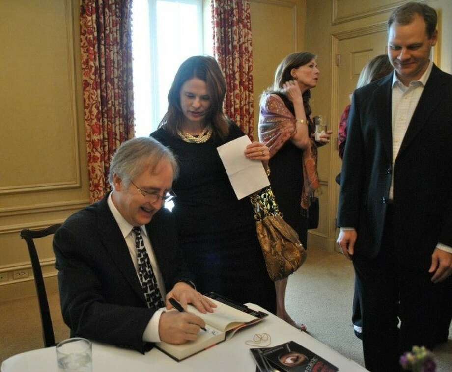 Best-selling author Raymond Benson signs autographs at the recent Family Portrait Luncheon fundraiser for the Alzheimer's Association, Houston and Southeast Texas Chapter.