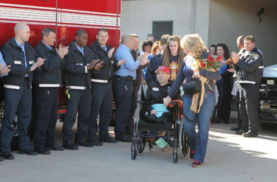 Houston Fire Department's Capt. Bill Dowling is released from Memorial Hermann Texas Trauma Institute and cheered by his company, Engine 68. Dowling will be to enjoy the holidays at home with his family after being injured in the Southwest Freeway hotel fire on May 31. Photo: Alan Warren