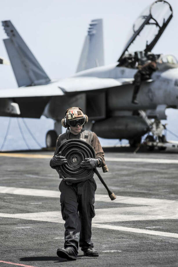 U.S. Navy Aviation Structural Mechanic Airman Brandon McNaughton, assigned to Strike Fighter Squadron (VFA) 147, carries a coiled hose across the flight deck of the aircraft carrier USS Nimitz (CVN 68) Aug. 28, 2013, in the Gulf of Oman. The Nimitz Carrier Strike Group was deployed to the U.S. 5th Fleet area of responsibility conducting maritime security operations and theater security cooperation efforts in support of Operation Enduring Freedom. Photo: U.S. Navy Photo By Mass Communication Specialist 3rd Class Chris Bartlett