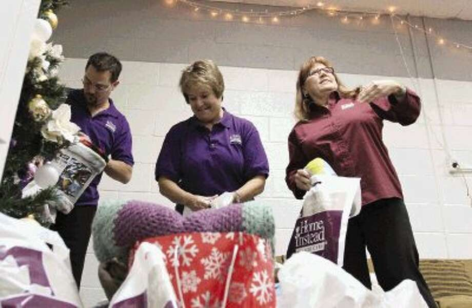 Kent Caballero, Sharon LaCoste and Annette Neyman helps stuff blankets into bags at Home Instead Senior Care Wednesday. The organization is giving blankets to seniors who might not otherwise receive gifts this holiday season. / Jason Fochtman