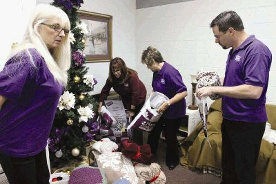 Sherri Wood, Annette Neyman, Sharon LaCoste and Kent Caballero helps stuff blankets into bags at Home Instead Senior Care Wednesday. The organization is giving blankets to seniors who might not otherwise receive gifts this holiday season. / Jason Fochtman