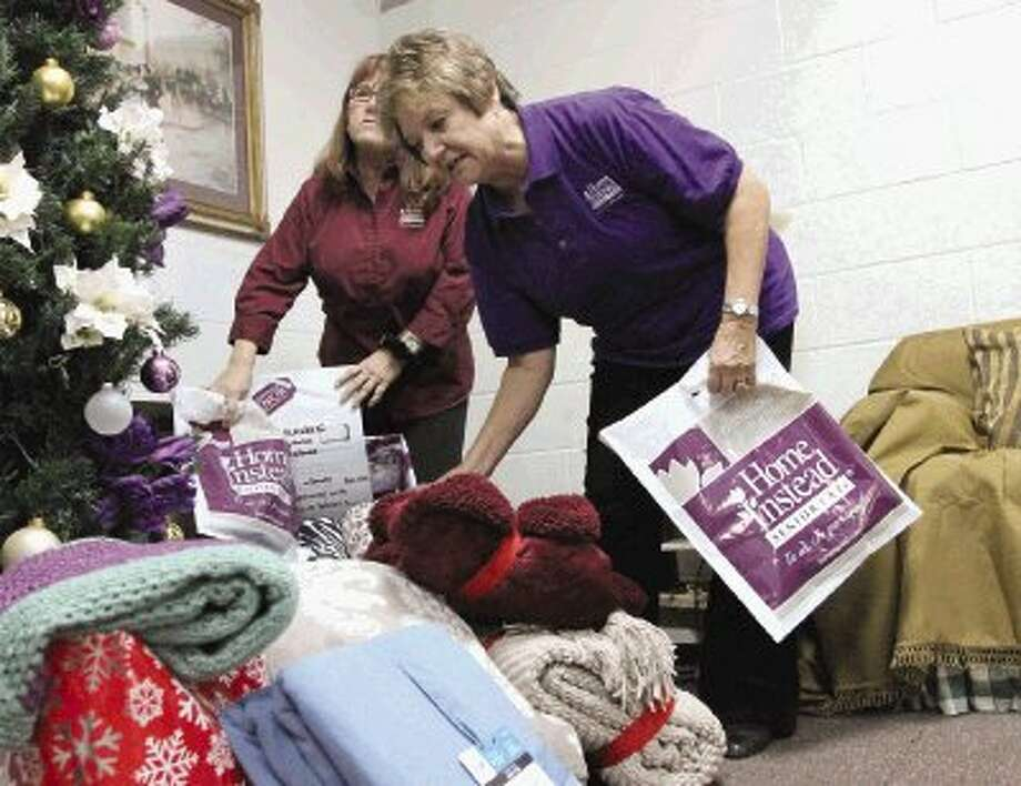 Sharon LaCoste helps stuff blankets into bags at Home Instead Senior Care Wednesday. The organization is giving blankets to senior citizens who might not otherwise receive gifts this holiday season. / Jason Fochtman