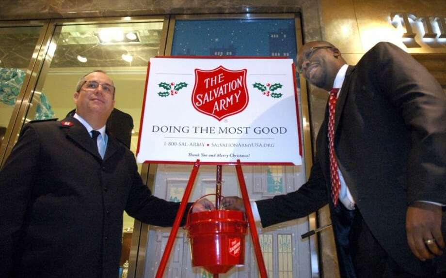 Salvation Army Maj. Chris Flanagan (left) and Michael McClure of Tiffany and Co. on Friday make the symbolic first donations to the Houston area's Red Kettle Campaign. Photo: Rusty Graham