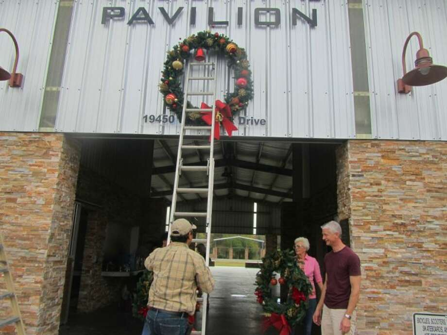 Daniel Reynosa of Daniel's Landscaping and Glenn Addison of Addison funeral home help hang the wreaths at the Pavilion.