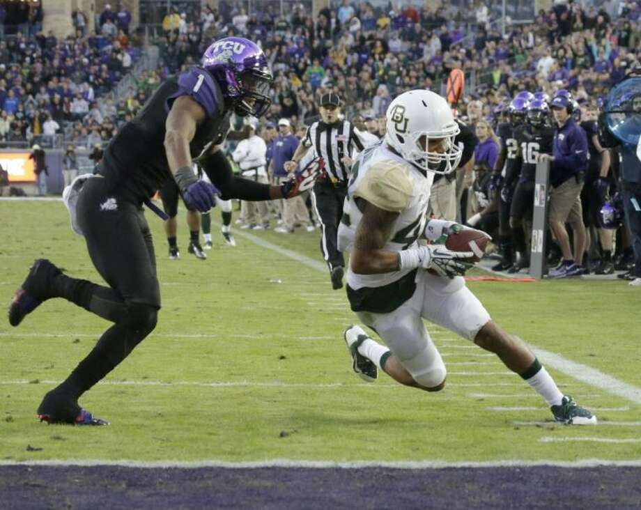 Baylor's Levi Norwood, right, scores a touchdown asTCU safety Chris Hackett gives chase in Fort Worth. Baylor won 41-38.