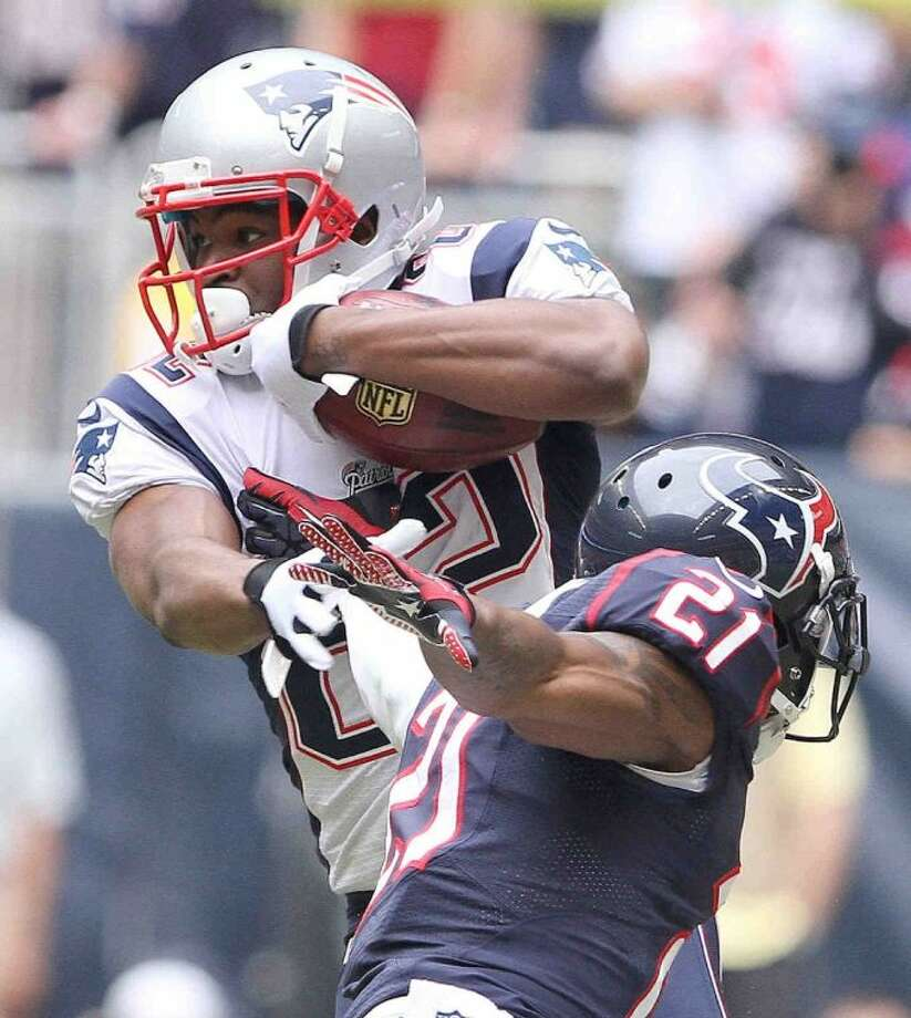New England Patriots wide receiver Josh Boyce (82) tries to break a tackle by Houston Texans cornerback Brice McCain in the first half. The Patriots edged the Texans 34-31.