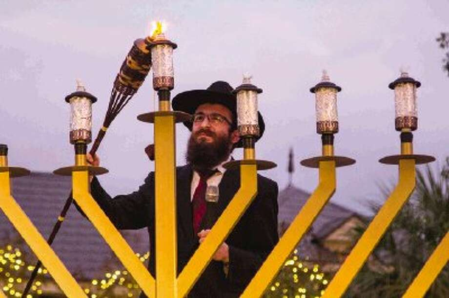 Rabbi Mendel Blecher lights a nine-foot menorah during the third Grand Hanukkah Celebration and Menorah Lighting at Market Street on Sunday in The Woodlands. Chabad of The Woodlands hosted the event to celebrate Hanukkah. The first 'Cannorah,' a menorah made of cans, was also lit and will later be donated to the Montgomery County Food Bank. Go to HCNPics.com to view and purchase this photo, and others like it. / The Conroe Courier/ The Woodland