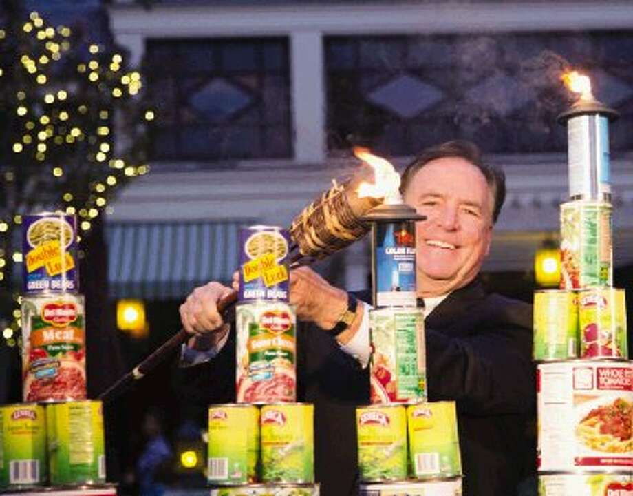 Bruce Tough, president of The Woodlands Township, lights the first-ever 'Cannorah' in The Woodlands / The Conroe Courier/ The Woodlands Villager