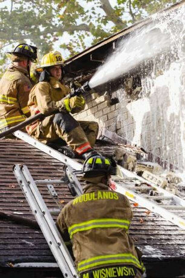 This crew of firefighters sprayed foam on the roof of a residence as Magnolia and The Woodlands fire departments responded to a fire Sunday afternoon at Whispering Pines, south of FM 1488. / The Conroe Courier/ The Woodlands Villager/ The Spring Observer
