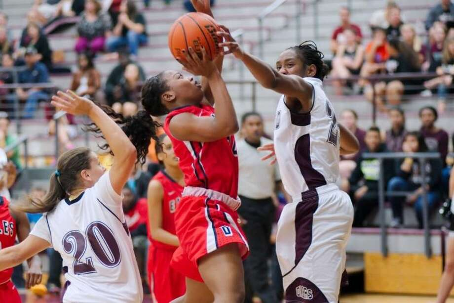 Dawson's Corlissa Charles (14) faces tough defense from Pearland's Jasmine Butler (25) and Miranda LeJune Tuesday night. The Lady Oilers defeated the Lady Eagles, 75-36. Photo: KIRK SIDES