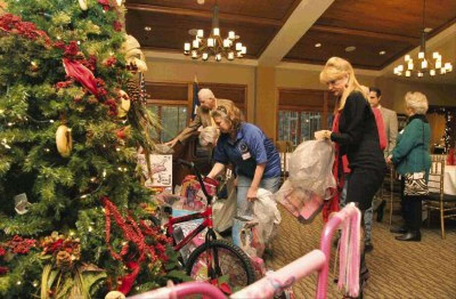 Nelda Blair and Debbie Bandfield place toys near a Christmas tree during the Third Annual Toys for Tots Montgomery County Precinct 3 Donation Party at The Woodlands Country Club Tuesday. Many state, county, and city officials and employees, business men and women and voters attended the Christmas party with Precinct 3 Commissioner James Noack. Guests were asked to bring a toy to donate for the Toys for Tots charity that gives toys to needy children in Montgomery County / Conroe Courier