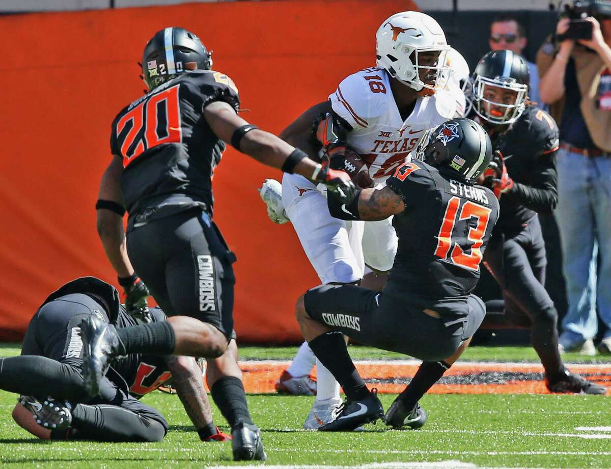 Texas quarterback Tyrone Swoopes (18) escapes Oklahoma State defenders Jordan Burton (20), Jordan Sterns (13) and Ramon Richards (7) and takes the ball in for a touchdown in the second quarter of an NCAA college football game in Stillwater, Okla., Saturday, Oct. 1, 2016. (AP Photo/Sue Ogrocki)