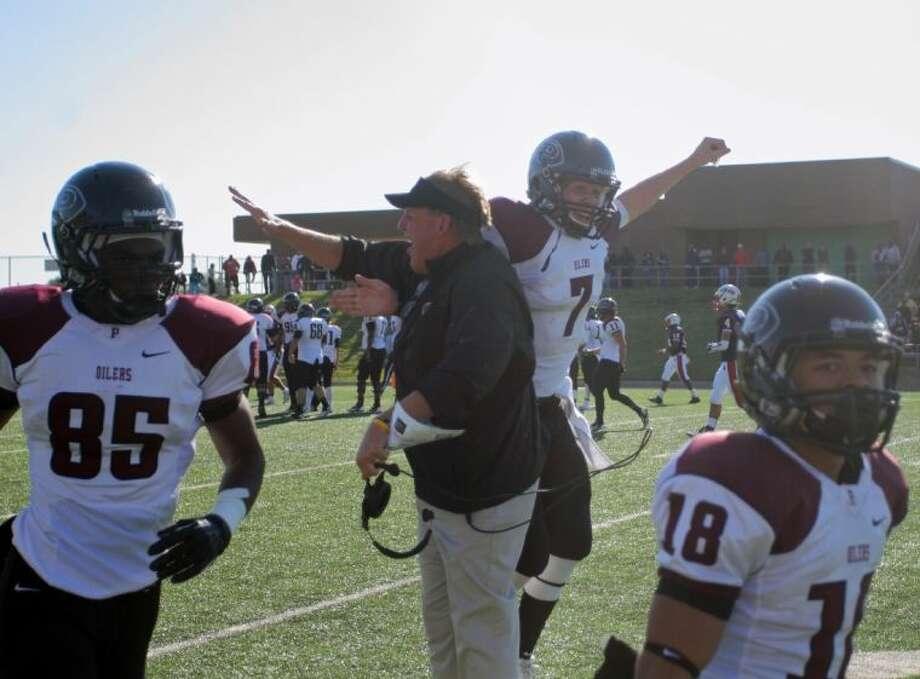 Pearland head coach Tony Heath celebrates with his son, Oiler quarterback Connor Heath following the latter's 80-yard touchdown pass to JaColbie Butler Friday against Houston Lamar. Photo: KAR HLAVA