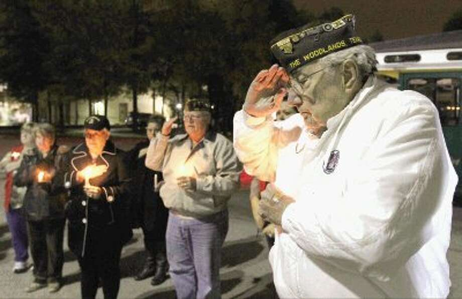 Dutch Dettinger, who served in World War II, Korea and Vietnam, salutes during a ceremony in remembrance of the Dec. 7, 1941 attacks on Pearl Harbor on Thursday. Dettinger joined members of Veterans of Foreign War Post 12024 who gathered to lay a wreath in a candlelight ceremony before the flag pole at the South County Community Center in honor of those who lost their lives in the Pearl Harbor attack. Photo: Staff Photo By Jason Fochtman / Conroe Courier