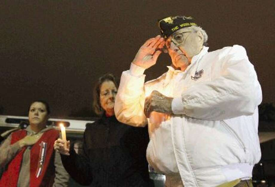 Dutch Dettinger, who served in World War II, Korea and Vietnam, salutes during a ceremony in remembrance of the Dec. 7, 1941 attack on Pearl Harbor Thursday. Members of Veterans of Foreign War Post 12024 gathered at the flag pole at the South County Community Center to pay their respects to those who lost their lives in the attack. Photo: Staff Photo By Jason Fochtman / Conroe Courier