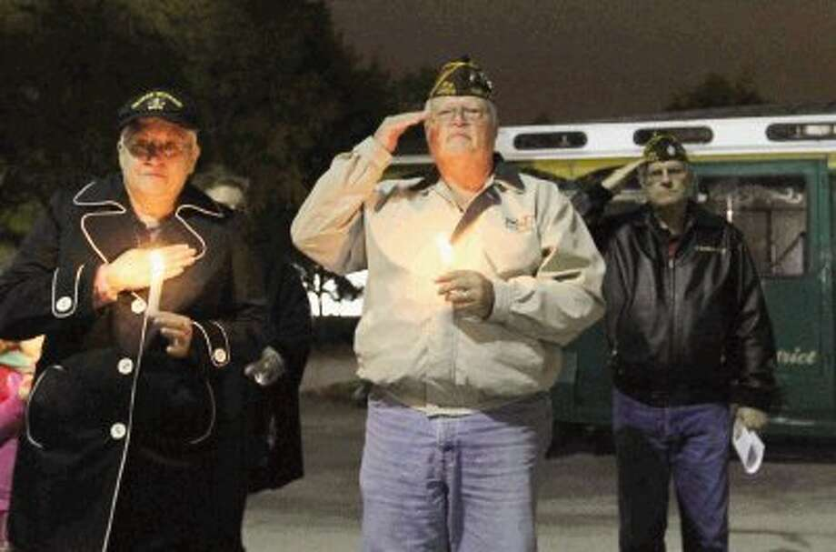 Members of Veterans of Foreign War Post 12024 salute during a ceremony in remembrance of the Dec. 7, 1941 attack on Pearl Harbor Thursday. Members gathered at the flag pole at the South County Community Center to pay their respects to those who lost their lives in the attack. Photo: Staff Photo By Jason Fochtman