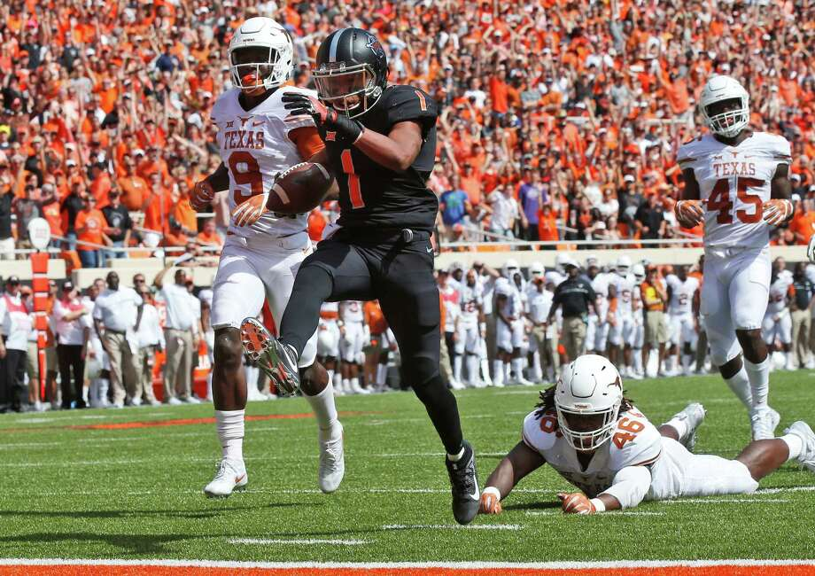 Oklahoma State wide receiver Jalen McCleskey (1) heads into the end zone with a touchdown in front of Texas cornerback Davante Davis (9), Malik Jefferson (46) and Anthony Wheeler (45) in the second quarter of an NCAA college football game in Stillwater, Okla., Saturday, Oct. 1, 2016. (AP Photo/Sue Ogrocki) Photo: Sue Ogrocki, Associated Press / AP2016