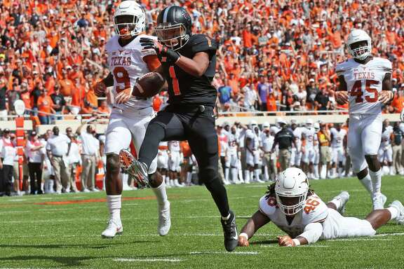 Oklahoma State wide receiver Jalen McCleskey (1) heads into the end zone with a touchdown in front of Texas cornerback Davante Davis (9), Malik Jefferson (46) and Anthony Wheeler (45) in the second quarter of an NCAA college football game in Stillwater, Okla., Saturday, Oct. 1, 2016. (AP Photo/Sue Ogrocki)