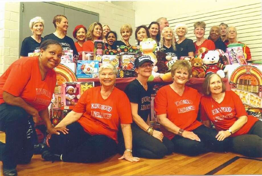 Behind a table of various toys and teddy bears, are Kingwood dancers, left to right, Martha Mierendorf, Shirley Rickett, Marva Alsander, Connie Shifferd, Glenda Williamham, Nel Guneratne , Louise Fisher, Wendy Bonds, Ressie Hobgood, John Shifferd, Dorothy Inglis, Sharon Ruby, Darlene Lemesh, Joyce Graves, Gary Floyd and Pat Floyd. In front of the table of toys are left to right Joyice Garrick, Juanita Jordan, Petra Ringeisen, Kay Caffey and Ruth Havens.