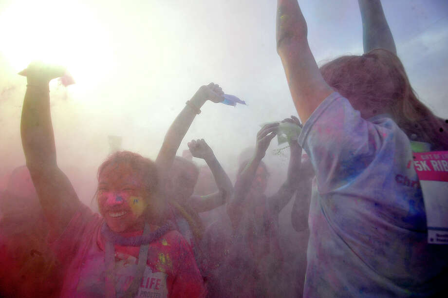 Participants celebrate as they take part in the final color blast during the Gift of Life's 6th annual Julie Richardson Procter 5K Ribbon Run Color Rush Saturday in downtown Beaumont. Photo taken Saturday, October 1, 2016 Kim Brent/The Enterprise Photo: Kim Brent / Beaumont Enterprise
